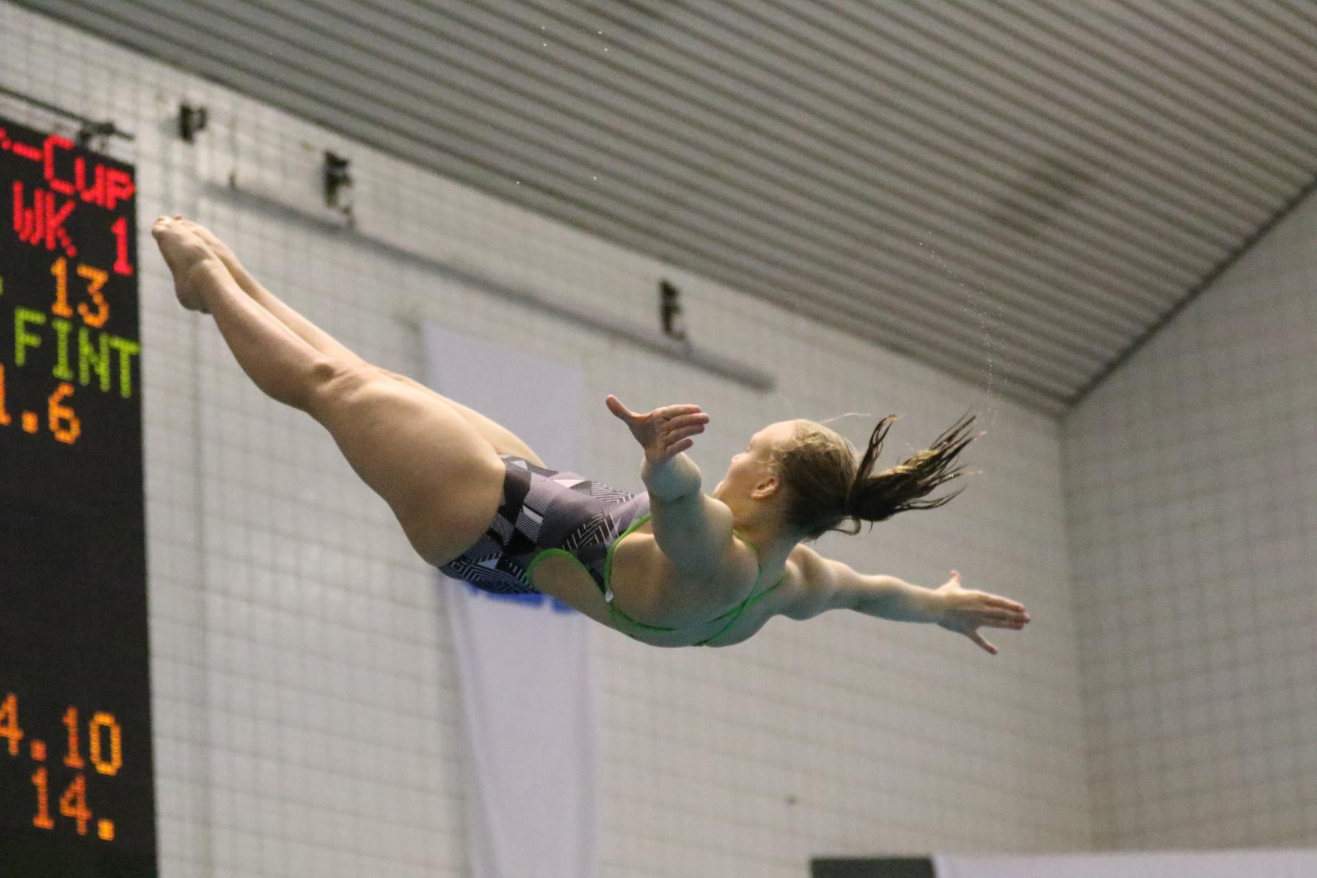 Uimahyppääjä ilmassa selällään, kasvot ylöspäin kädet suorana sivuilla nilkat ojennettuna