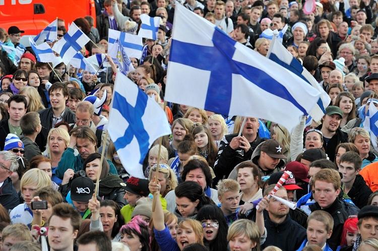 Paljon ihmisiä liehuttamassa Suomenlippuja