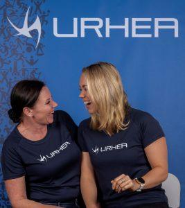 Kaksi naishenkilöä nauravat kasvot toisiaan vasten