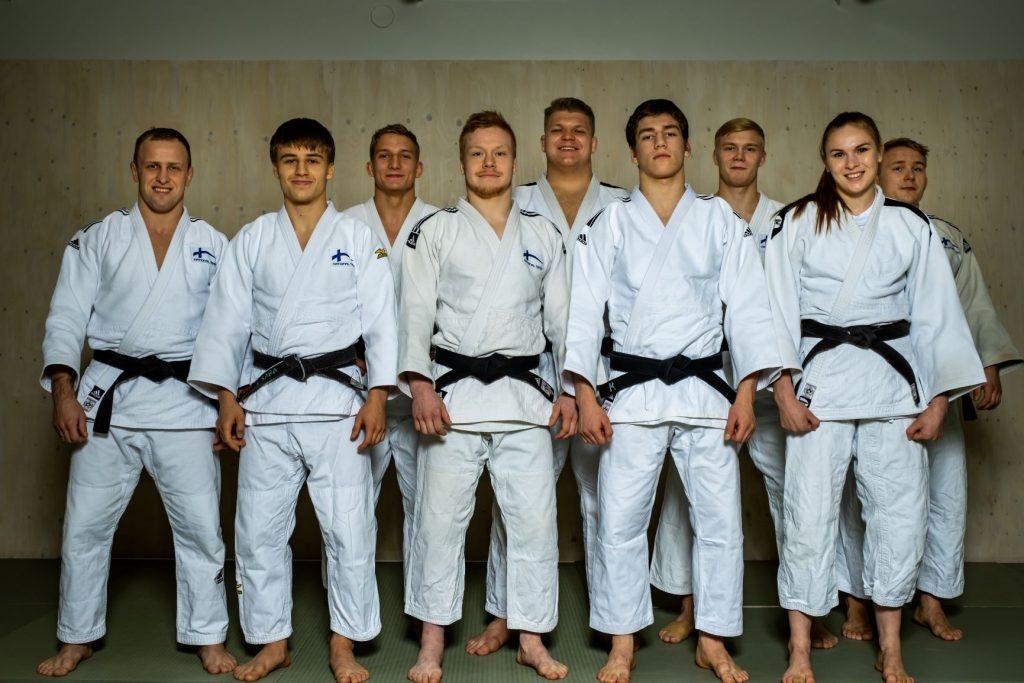 Yhdeksän judokaa seisoo judoasut päällä kädet suorina sivulla kameraan päin ja hymyilee