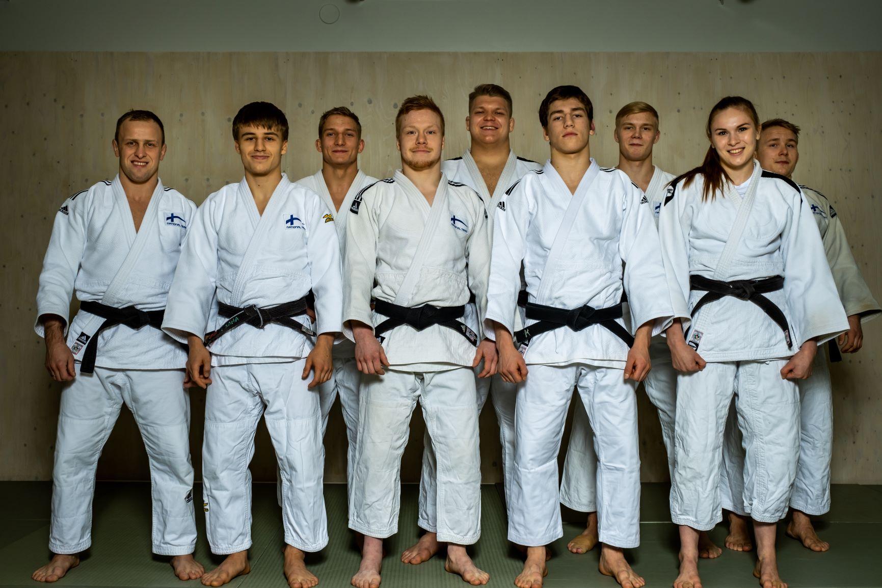 9 judokaa seisoo ryhmänä kasvot kameraan päin ja hymyilee