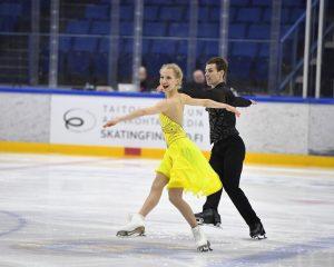 Jäätanssijapari jäällä, naisella keltainen mekko ja miehellä kokomusta asu