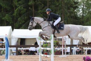 Ratsastaja hyppää esteen yli vaalealla ratsuhevosella