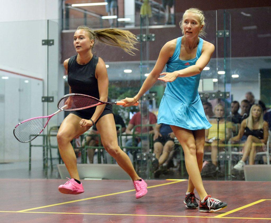 Kaksi squashinpelaajaa kesken pelin squashkentällä vierekkäin liikkumassa eri suuntiin