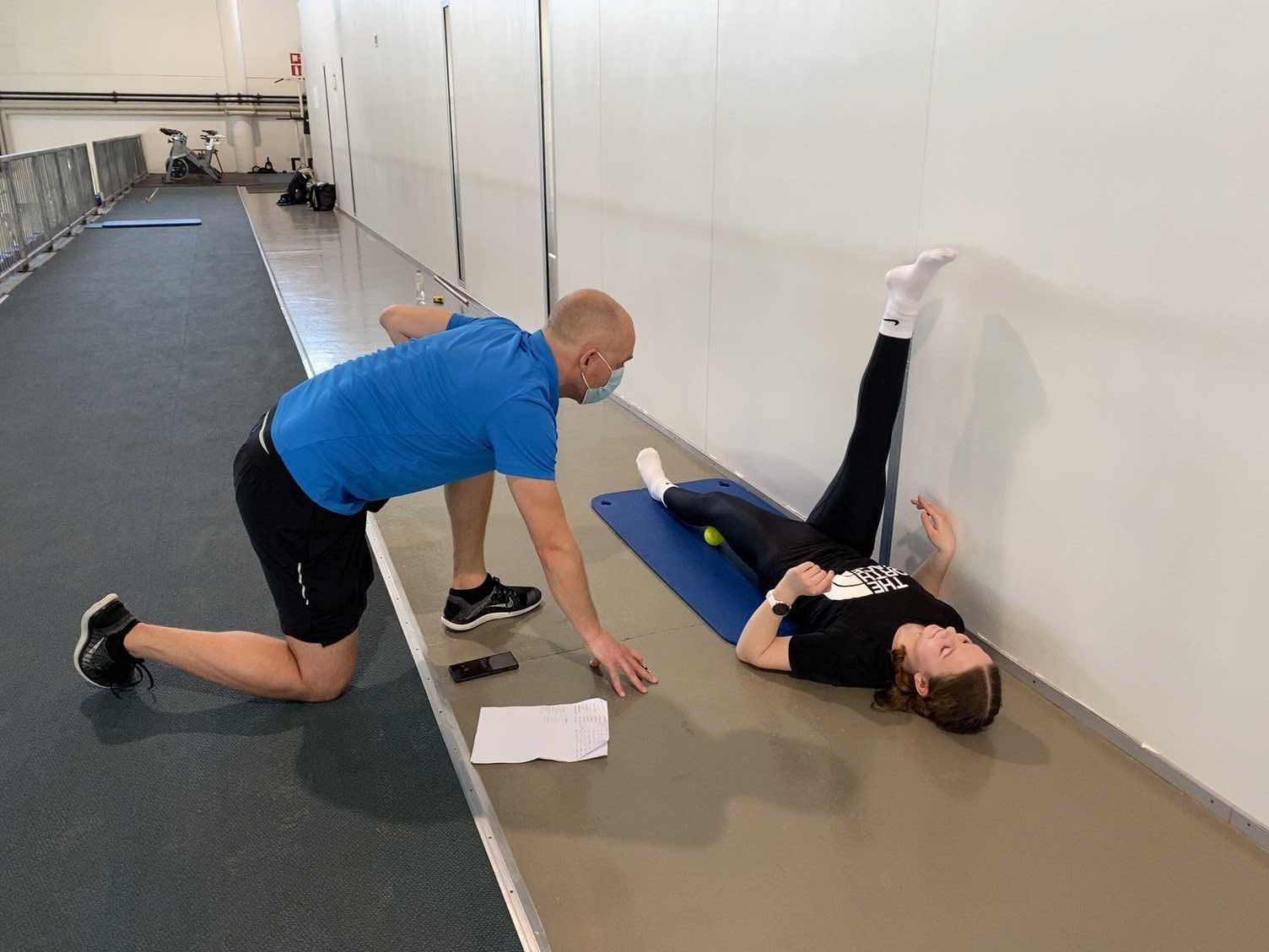Valmentaja on lattiantasossa toinen polvi lattiassa, seuraa selällään olevaa urheilijaa, jonka toinen jalka on ilmassa seinää vasten