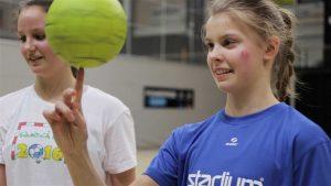 Tyttö pitää pyörivää palloa etusormensa päällä