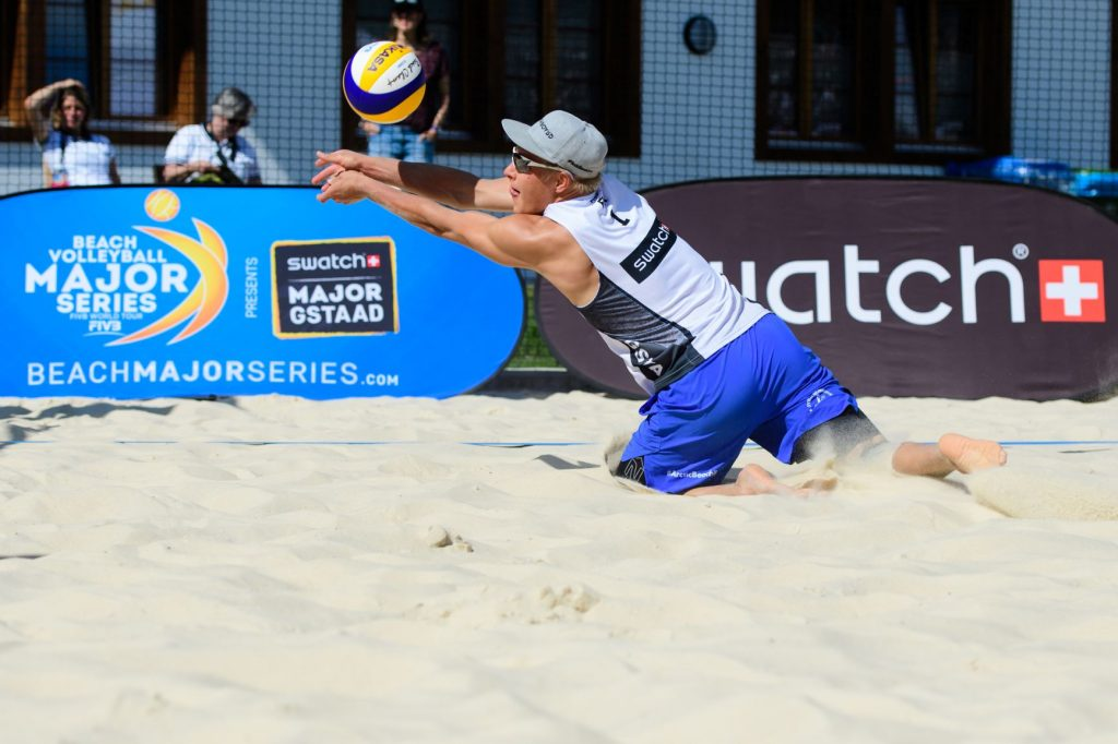 Beach volley -pelaaja polvillaan hiekassa lyömässä palloa