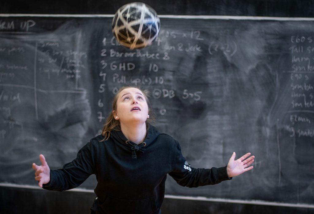 Tyttö pomputtaa palloa päällään liitutaulun edessä