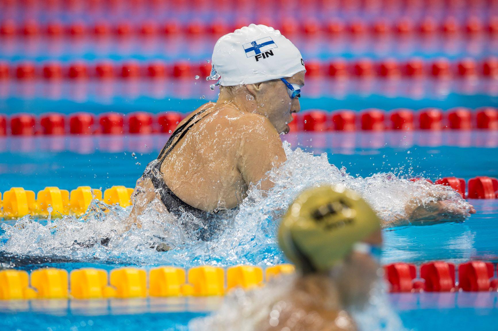 Kaksi uimaria ui rintauintia uintiradoillaan
