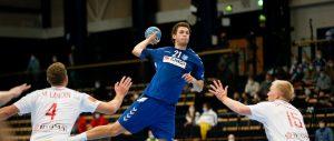 Mies heittää käsipalloa ilmassa, kaksi vastustajaa puolustaa