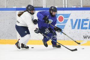 Kaksi jääkiekkoilijaa kamppailee kiekosta kaukalossa