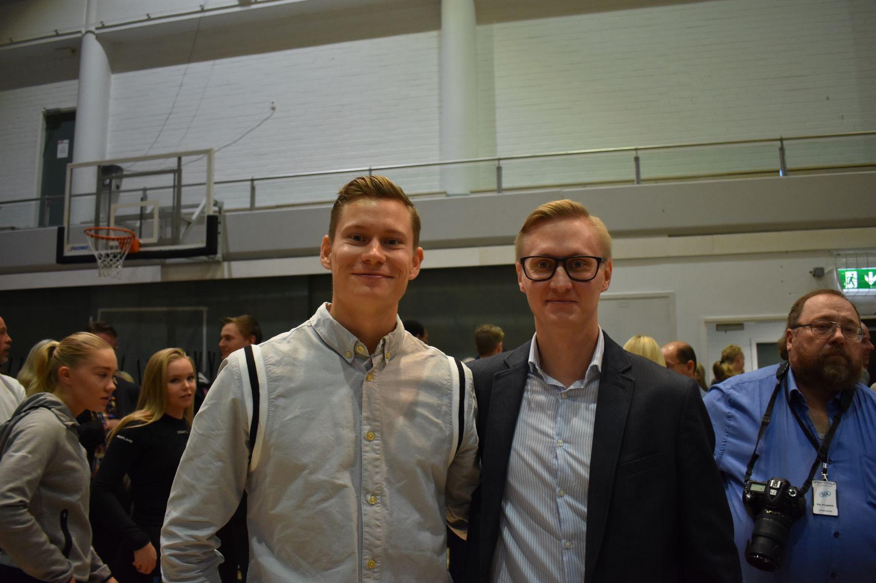 Kaksi miestä seisoo vierekkäin katse kameraan päin ja hymyilee