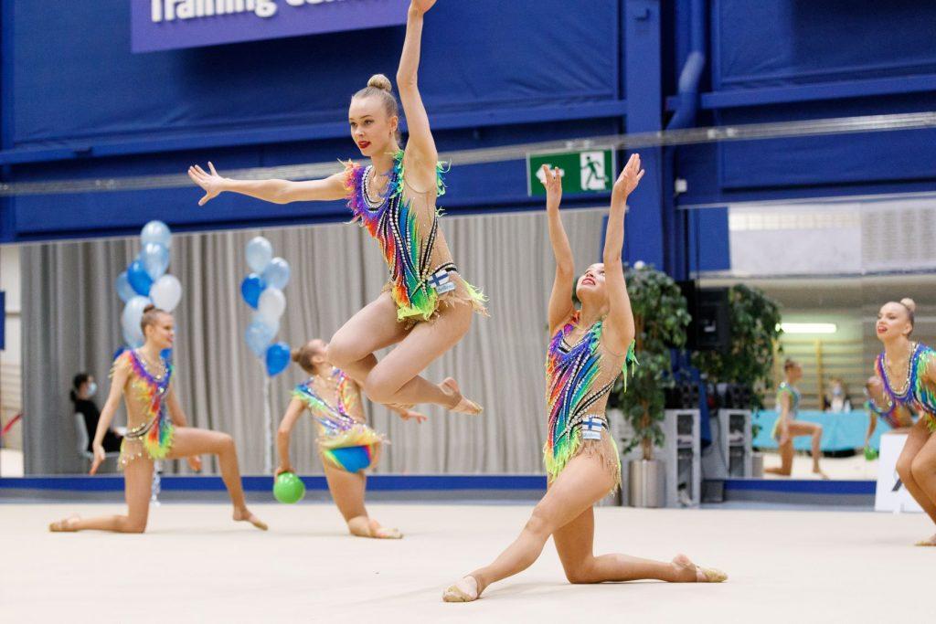 Suomen rytmisen voimistelun maajoukkue voimistelee värikkäät kilpailuasut päällä, yksi voimistelijoista on hypännyt ilmaan, neljä muuta voimistelijaa permannolla toinen polvi lattiassa.