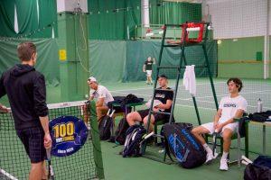 Tenniskentällä kolme pelaajaa istuu kentän laidalla tuoleilla ja katsoo kohti valmentajaa, joka seisoo verkon vieressä