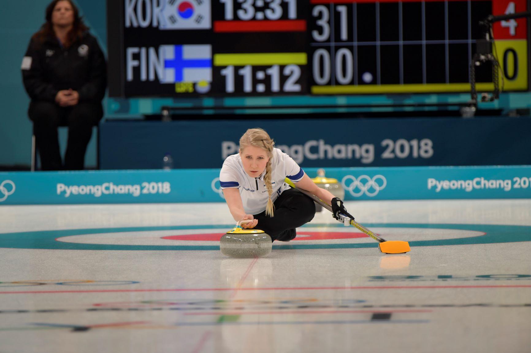 Curlingpelaaja pitää kiinni kivestä ja liukuu jäällä