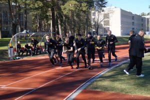 Joukko nuoria miehiä juoksee juoksuradalla