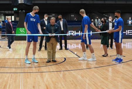 Pormestari Juhana Vartiainen leikkaa Urhea-hallin avajaisnauhaa hallin parketilla Helsinki Basketball Academyn pelaajien avustaessa