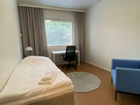 Ikkunallinen huone, jossa on sänky, kirjoituspöytä ja tuoli sekä nojatuoli
