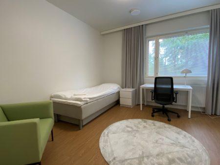 Ikkunallinen huone, jossa on nojatuoli, sänky, yöpöytä, kirjoituspöytä ja tuoli