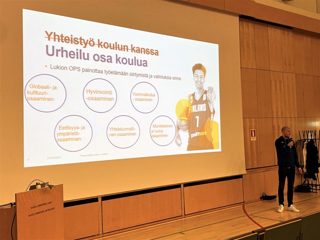 """Juha Sten puhuu auditoriossa, heijastettuna dia jossa on yliviivattuna teksti """"Yhteistyö koulun kanssa"""" ja alla lukee otsikkona """"urheilu on osa koulua"""""""