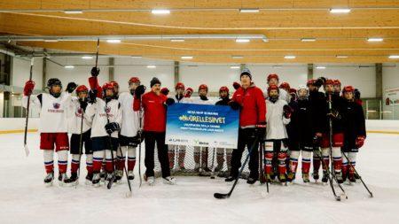 """joukko nuoria jääkiekkoilijoita seisoo ryhmässä jäällä, mukana kaksi valmentajaa, pitelevät Nuorelle siivet -stipendiä jossa lukee """"lahjoituksen ansiosta saamme ammattivalmentajan lukukaudeksi"""""""